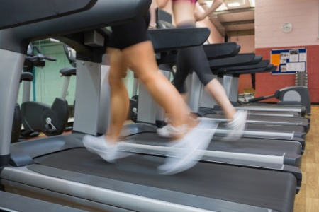 Two people running on treadmills in the gym